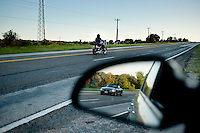 A motorcycle drives past heads past Highway 281 as another car is reflected in a rear view mirror in Hill Country, Texas, on April 26, 2010. The historic highway offers many attractions including Fossil Rim Nature Park, many spring time flowers, and a wonderful view of hill country in central Texas...PHOTOS/ MATT NAGER