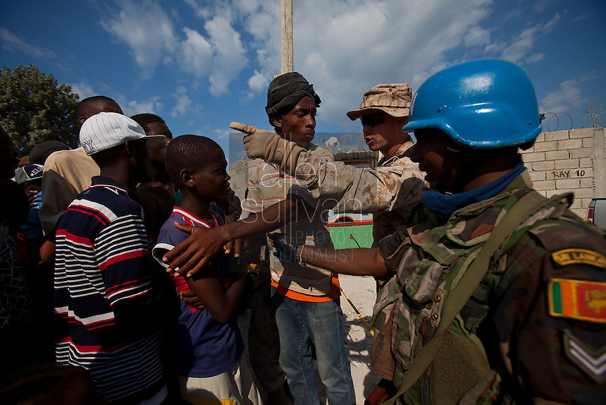 A Haitain man, U.S. Marine and Sri Lankan U.N. soldier help organize a line for food tickets west of Port-au-Prince. The 7.0 earthquake that devastated parts of Haiti on January 12 killed hundreds of thousands of people. January's earthquake killed hundreds of thousands of people and caused significant and lasting structural and economic damage in the Caribbean nation.