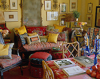 Brightly accented cushions from different cultures and periods work well on an eighteenth century lacquered sleigh bed in this living room