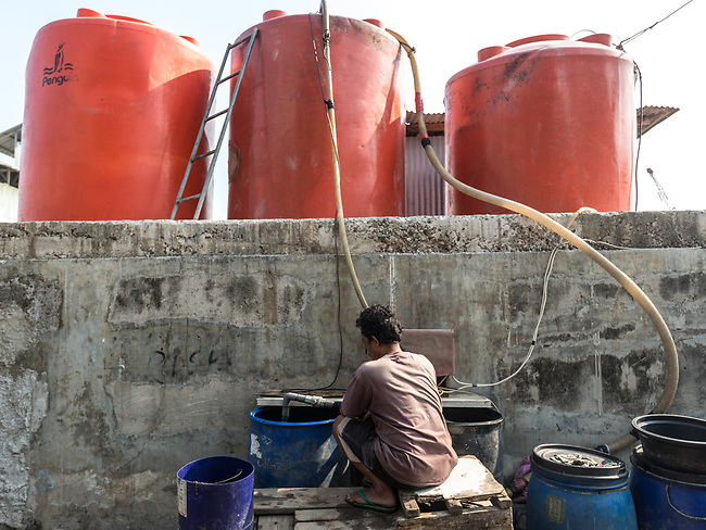 13 August 2019, Jakarta, Indonesia: A local man loads up water barrels sitting on the seawall to sell on the  streets of Muara Baru, North Jakarta. Local residents were speaking about the lack of water facilities that the local poor population has access to. Water is hauled in each day by motorcycle and trucks and by hand to allow residents of the kampungs to  buy it for washing and to do laundry. Separate water is needed for drinking. The Jakarta Governor is proposing a program to send in trucks of water for the locals to get for free. They are living in villages below the seawater line on the coast of Jakarta that is sinking faster than anywhere else in the world so they have the position of being surrounded by water yet not having access to clean supplies. Picture by Graham Crouch/The Australian