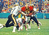 Washington Redskins running back Clarence Harmon (38) carries the ball against the New Orleans Saints at Robert F. Kennedy Stadium in Washington, DC on October 28, 1979.  Defending on the play are Saints strong safety Ray Brown (27), defensive tackle Mike Fultz (72) and left defensive end Elois Grooms (78).  The Saints won the game 14 - 10.   <br /> Credit: Arnie Sachs / CNP