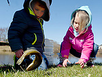 Cole Sullivan, 3, of South Windsor, left,  and his twin sister Taryn, watch with amazement as the fish they were attempting to take from the bucket to release back it back into the pond flips in the air, during the 34th annual South Windsor fishing derby, Saturday, April 21, 2018, at the pond on Barber Hill Road in South Windsor. One-hundred-and-seventy-five trout were stocked in the pond for the event which was sponsored by the Park and Recreation and Human Services departments and the Super 60's Sportsmen Club.   (Jim Michaud / Journal Inquirer)