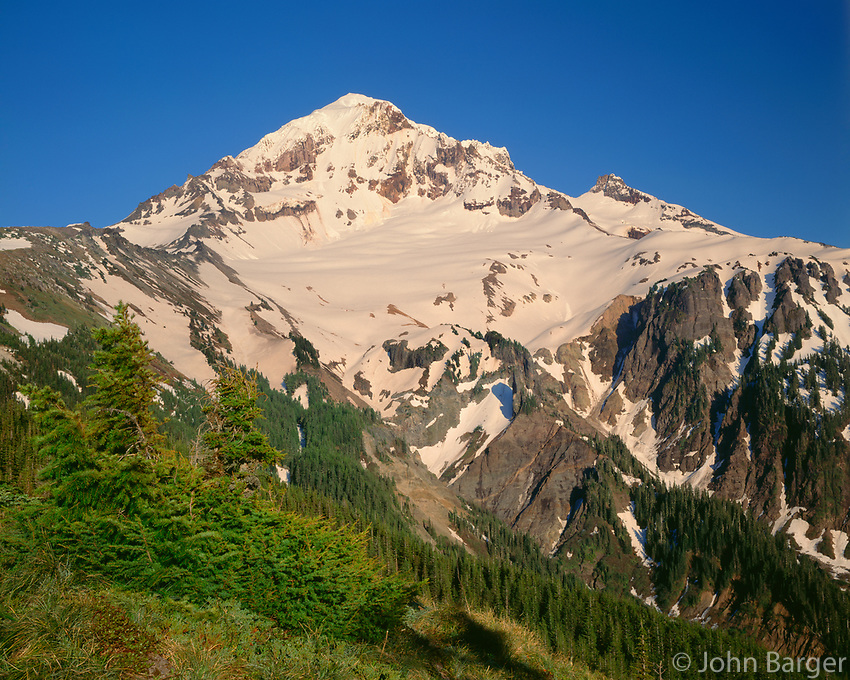 USA, Oregon, Mount Hood National Forest, Mount Hood Wilderness, Evening light on the west side of Mount Hood in early summer with lingering snow pack from previous winter.
