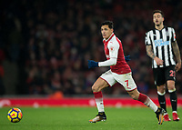 Alexis Sanchez of Arsenal runs past Joselu of Newcastle United during the Premier League match between Arsenal and Newcastle United at the Emirates Stadium, London, England on 16 December 2017. Photo by Vince  Mignott / PRiME Media Images.