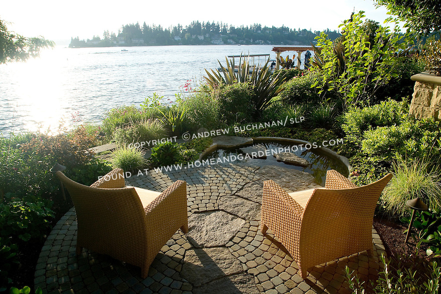 two wicker armchairs sit in the late afternoon summer sun on a small, private circular patio with a waterside view of the lake, surrounded by lush gardens.  Design by Sander Groves Landscapes, Inc., and Linda Attaway Landscape Architect.