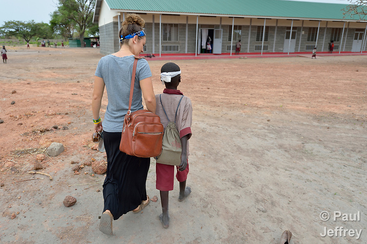 Nicky Hess, a Mennonite volunteer from the United States,  walks with an injured boy towards the clinic of the Loreto School in Rumbek, South Sudan. The school is run by the Institute for the Blessed Virgin Mary--the Loreto Sisters--of Ireland. Hess is an emergency room nurse from Lancaster, Pennsylvania.
