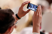 Papa Francesco celebra la Santa Messa del Crisma nella Basilica di San Pietro, Citta' del Vaticano, 28 marzo 2013..A priest uses his mobile phone to take pictures as Pope Francis celebrates the Chrism Mass in St. Peter's Basilica at the Vatican, 28 March 2013..UPDATE IMAGES PRESS/Riccardo De Luca..STRICTLY ONLY FOR EDITORIAL USE