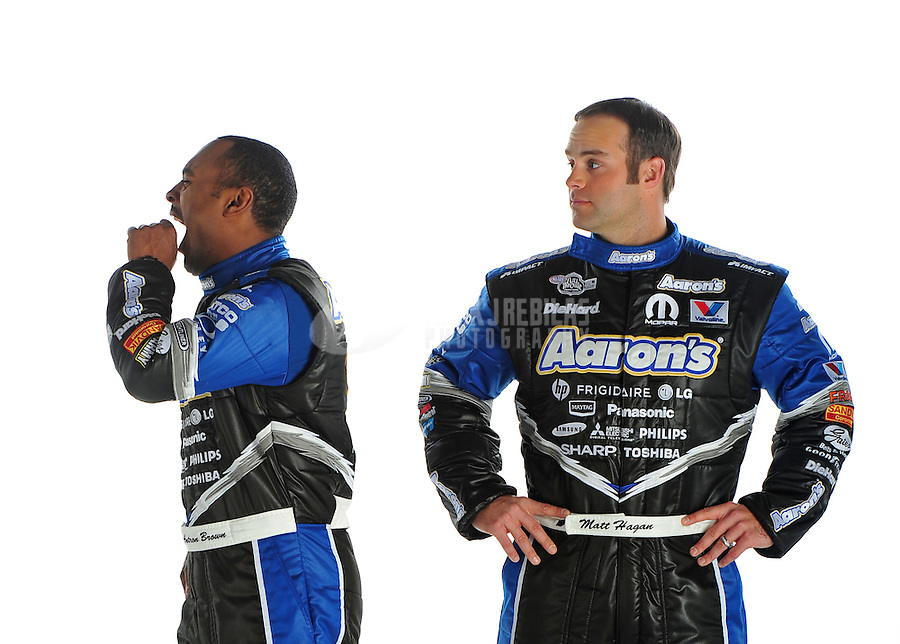 Jan. 8, 2012; Brownsburg, IN, USA; NHRA top fuel dragster driver Antron Brown (left) yawns as funny car driver Matt Hagan looks on during a photo shoot at the Don Schumacher Racing shop. Mandatory Credit: Mark J. Rebilas-
