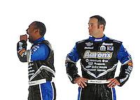 Jan. 8, 2012; Brownsburg, IN, USA; NHRA top fuel dragster driver Antron Brown (left) yawns as funny car driver Matt Hagan looks on during a photo shoot at the Don Schumacher Racing shop. Mandatory Credit: Mark J. Rebilas-