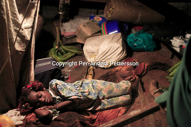 LUKUTU, DEMOCRATIC REPUBLIC OF CONGO MARCH 13: Noella Ndomte, age 8, sleeps under deck on a boat traveling on the Congo River from Kisangani to Kinshasa, the capital on March 13, 2006 in Lukutu, Congo, DRC. The Congo River is a lifeline for millions of people, who depend on it for transport and trade. The journey from Kisangani to Kinshasa is about 1750 kilometers, and it takes from 3-7 weeks on the river, depending on the boat. During the Mobuto era, big boats run by the state company ONATRA dominated the traffic on the river. These boats had cabins and restaurants etc. All the boats are now private and are mainly barges that transport goods. The crews sell tickets to passengers who travel in very bad conditions, mixing passengers with animals, goods and only about two toilets for five hundred passengers. The conditions on the boats often resemble conditions in a refugee camp. Congo is planning to hold general elections by July 2006, the first democratic elections in forty years. (Photo by Per-Anders Pettersson)...