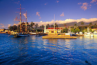 Lahaina Harbor at sunset. West Maui Mountains in the background, with Lahaina Town and Front Street to the far left. From left to right is the brig the Carthaginian III, Lahaina Light House, the main loading dock and the Pioneer Inn.