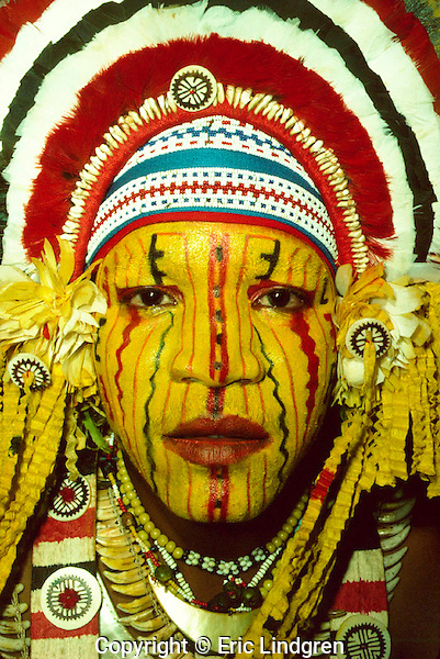 Head-dress and facial decoration on Mekeo youth, Papua New Guinea. Mekeo people come from the eastern parts of the Gulf Province and the western parts of the Central Province in south-central PNG. Their spectacular costuming (=bilas=decoration) favours use of bright yellow on face and body. Head-dresses are a characteristic shape and made from feathers of the Eclectus Parrot (red), Sulphur-crested Cockatoo (white) and domestic fowl (black). The round decorations are mother of pearl shell or giant clam shell overlaid with fret-worked tortoise-shell (=kapkap). The head-band is made from tiny beads of assorted colours. The shiny crescent-shaped necklet (=kina - also name for the 'dollar' coin in PNG currency) below the chin is  part of a Gold-lipped Pearl Shell.  //  Eclectus Parrot - Psittacidae: Eclectus roratus. Length to 43cm, wingspan to NNcm, weight to 550g. Male - green, female - bright red. In New Guinea widespread in lowland rain forests to 1000m. Also in Lesser Sunda Islands, Malukus (Moluccas), east to Solomon Islands. In Australia only in eastern Cape York rain-forests. //  Gold-lipped Pearl Shell - Pteriidae: Pinctada maxima. Much prized by Papua New Guineans and throughout the Pacific for use as body decorations. A pearl-producing oyster found in the south-west and central Pacific Ocean.  //Eric Lindgren//