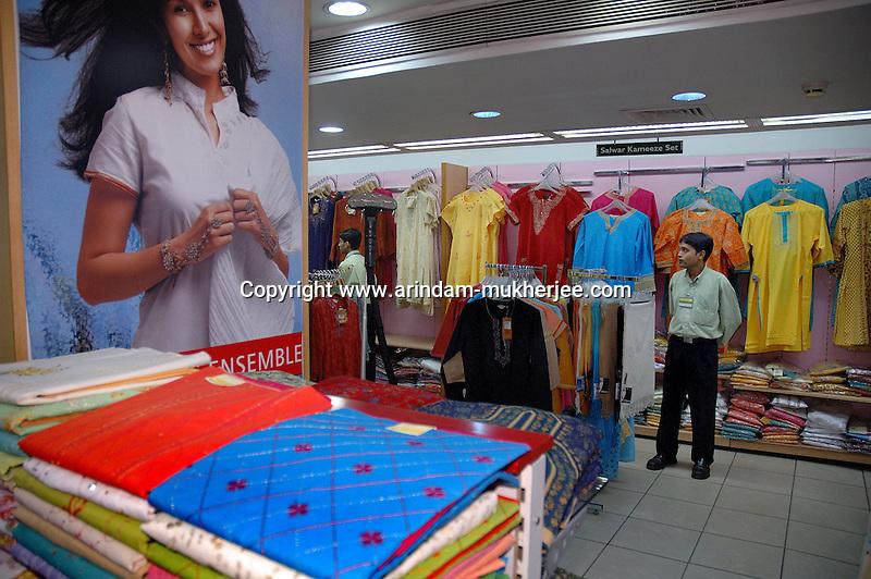 A shopping mall worker waits for customer at Pantaloons, Calcutta, India  Arindam Mukherjee
