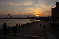 Dusk against the background of the Campanile tower and Basilica of St Marks square.  Grand canal . Foreground silhouetted people walking along dockside at Arsenale. Venice Italy.