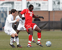 University of New Mexico midfielder Michael Kafari (10) controls the ball as University of Connecticut midfielder Adria Beso (11) closes..NCAA Tournament. With a goal in the second overtime, University of Connecticut (white) defeated University of New Mexico (red), 2-1, at Morrone Stadium at University of Connecticut on November 25, 2012.