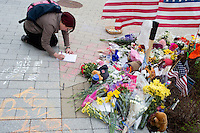 People gather at a small memorial for slain MIT police officer Sean Collier between the STATA Center and Koch Institute on MIT's campus in Cambridge, Mass., on April 20, 2013.  Collier was shot and killed by the Tsarnaev brothers, suspects in the Boston Marathon bombings earlier that week.