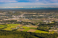 Aerial view of the city of Fairbanks situated in the Tanana valley flats, Creamer's Field in the foreground, the Alaska Range mountains visible on the distant horizon.