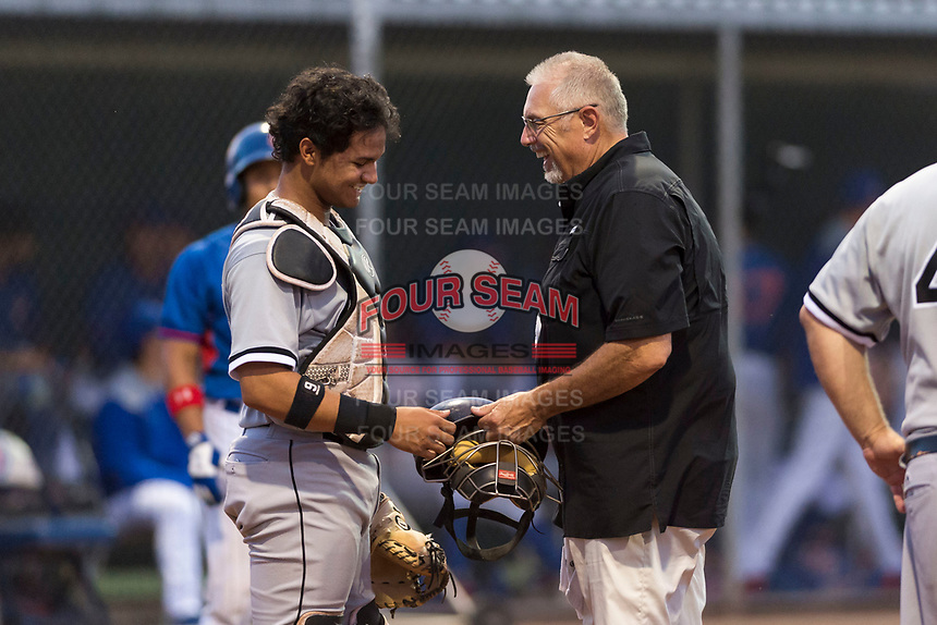 AZL White Sox athletic trainer Scott Johnson checks on catcher Kleyder Sanchez (28) during an Arizona League game against the AZL Cubs 2 at Sloan Park on July 13, 2018 in Mesa, Arizona. The AZL Cubs 2 defeated the AZL White Sox by a score of 6-4. (Zachary Lucy/Four Seam Images)