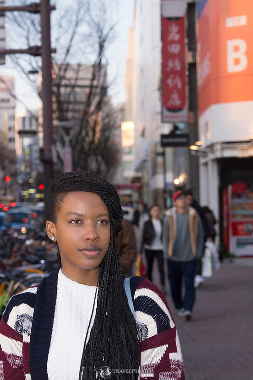 A young lady walking along the street in Japan.