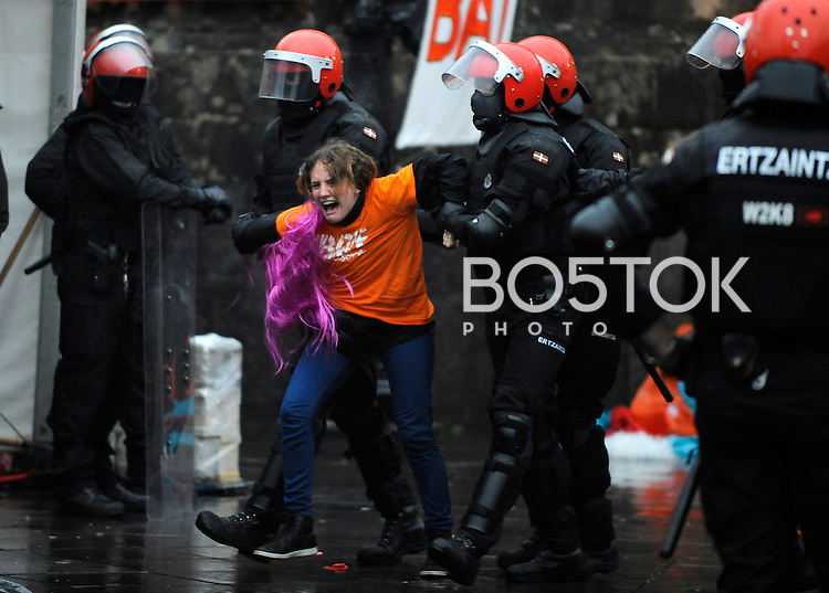 Basque police moves a girl out of the way in order to reach 5 young people on September 22, 2014 in Azpeitia, Basque Country. Hundreds of people gathered outside the Loiola Basilica to prevent the incarceration of Jazint Ramirez, Irati Tobar, Igarki Robles, Imanol Salinas and Xabier Arina after an arrest warrant was issued by the Spanish Court against them after they have not appeared in court for the start of a trial against 28 Basque youth accused of belonging to Basque youth organization SEGI. (Ander Gillenea / Bostok Photo)