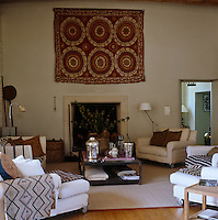 A group of white armchairs with ethnic fabrics and cushions surround the fireplace in the living room above which hangs a suzani textile