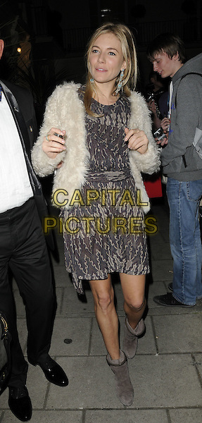 "SIENNA MILLER.Seen leaving after the evening performance of ""Flare Path"", Theatre Royal Haymarket, London, England, UK, April 7th 2011..full length white cream fur furry jacket beige grey gray ankle boots print dress.CAP/CAN.©Can Nguyen/Capital Pictures."