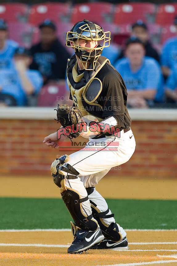 Catcher Brett Armour #6 of the Wake Forest Demon Deacons looks for the baseball as a bad throw goes to the backstop during the game against the Miami Hurricanes at Gene Hooks Field on March 18, 2011 in Winston-Salem, North Carolina.  Photo by Brian Westerholt / Four Seam Images