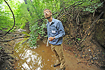 Riverkeeper Chris Trumbauer stands in a channel of the north fork of Muddy Creek cut deep by uncontrolled runoff. (Photo by Joshua McKerrow - The Capital) 07/14/10