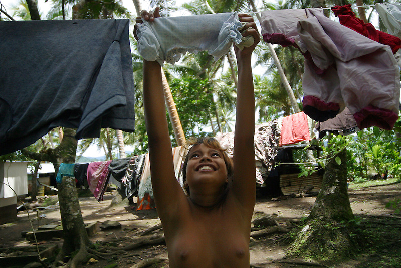 A young girl hangs laundery in the Federated States of Mirconesia.