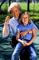 Grandparents and granddaughter on swing girl age 6