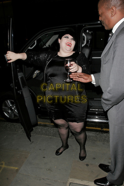 BETH DITTO.At the Hogan Store Party, Sloane Street, London, England, UK, May 13th 2009..full length black dress shiny silk satin fat overweight ripped tights cellulite ballet flats plumps glass of red wine drink hand arm getting out of car sequined jacket laughing funny .CAP/AH.©Adam Houghton/Capital Pictures