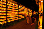 A young Japanse couple, wearing yukata or summer-weight kimono, look at yellow lanterns, each containing the name of a fallen military serviceman, during the Mitama matsuri or festival of remembrance at the controversial Yasukuni Shrine in Chiyoda, Tokyo, Japan. Tuesday, July 13th 2010