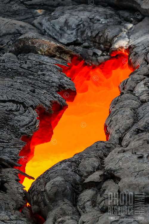 Earth Crack: A skylight opened up above a river of lava flowing rapidly in a tube directly below the viewer's feet, 61g flow, Hawai'i Volcanoes National Park, Big Island.