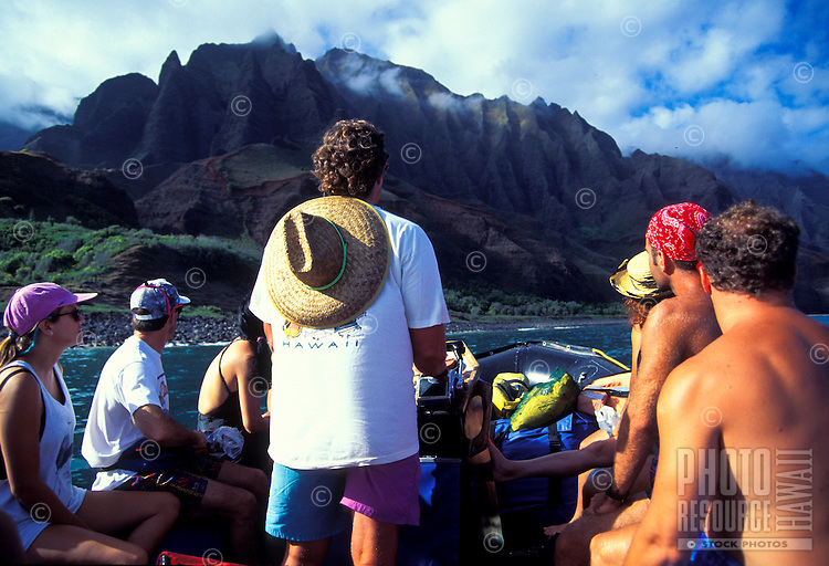 People riding a in a zodiac inflatable along Kauai's Na Pali northern coastline
