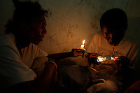 """John holds a candle to illuminate Steven  while doing drugs in an abandoned compound  in Monrovia, Liberia on  Wednesday March 21 2007..Melvin, 29 AKA """"Dad"""",  John, 29 AKA """"Desperate Soldier, Thomas 28 AKA """"Bullet Patrol"""", Leroy, 28, AKA """" Pussy Mechanic"""" and Steven 27 AKA """"Field Marshall"""" are all former child soldiers that found each other on the streets after the last round was fired in Liberia. Since then they """"Hustle"""" to put some food in their stomachs and buy some drugs to """" make them forget about their lives""""..ALL NAMES HAVE BEEN FICTIONALIZED TO PROTECT THE IDENTITIES OF THE 5 MEN."""