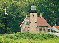 The White River Lighthouse and light station sits among summer trees in Montague, Michigan