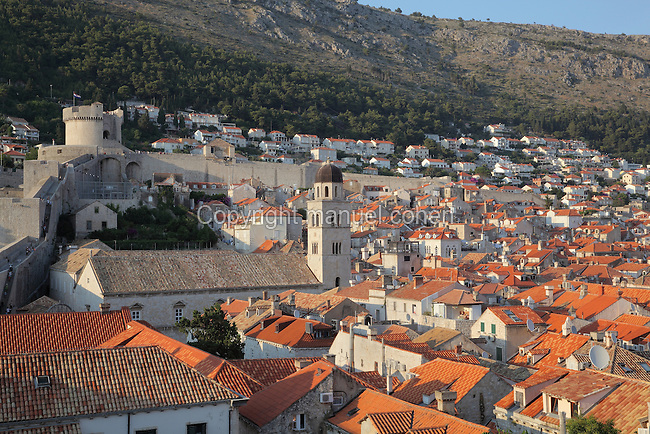 View across the rooftops of the Old Town, with the 14th century Franciscan monastery on Stradun or Placa, and the 14th century Minceta Tower on the city walls to the left, Dubrovnik, Croatia. The city developed as an important port in the 15th and 16th centuries and has had a multicultural history, allied to the Romans, Ostrogoths, Byzantines, Ancona, Hungary and the Ottomans. In 1979 the city was listed as a UNESCO World Heritage Site. Picture by Manuel Cohen