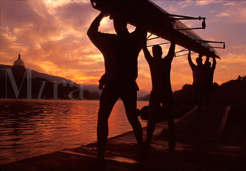 College rowers in silhouette carry their boat to a river for a dawn practice.