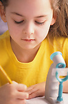Young girl 7 years old writing at school studying with microscope Bothell Washington State USA   MR