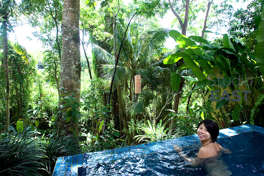 A young woman swims in a private villa's swimming pool in Komaneka hotel, in Ubud, Central Bali, Indonesia, on February 21, 2010. Photo by Lucas Schifres/Pictobank