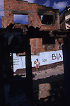 An Albanian boy raises a Kosovo Liberation Army salute amidst the burnt remains of a Kosovar Roma Gypsy home in the Park district. UCK graffiti is on the walls. The Roma's houses were razed to the ground by returning Albanians, helped back by the UN after the Kosovo War. The Albanians accused Roma of supporting the Serbs, and forced tens of thousands of Roma from Kosovo in an act of ethnic cleansing. Pristina, Kosovo 1999