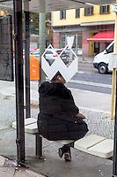 Berlino, quartiere Kreuzberg. Una donna con le cuffiette seduta alla pensilina (del marchio Wall AG) di una fermata dell'autobus --- Berlin, Kreuzberg district. A woman with earphones sitting at the bus stop shelter (of the brand Wall AG)