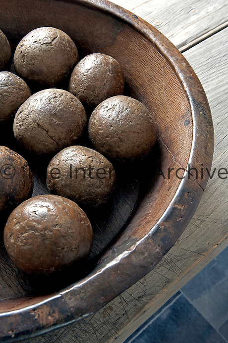 Detail of an antique walnut bowl containing an ancient set of boules made from boxwood