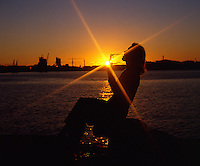 Silhouette of girl wearing sunglasses against a harbour and an urban background. Sydney 1980.
