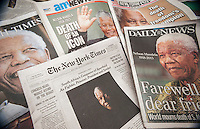 New York newspaper covers on Friday, December 6, 2013 report on the death of South African civil rights activist Nelson Mandela at the age of 95. (© Richard B. Levine)