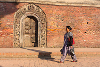 Nepal, Patan.  Nepali Woman Walking by Doorway into Royal Palace Compound, Durbar Square.