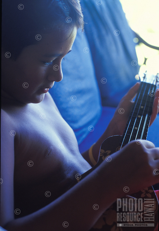 Local Hawaiian boy playing ukulele at home