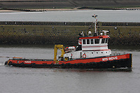 A tugboat MTS Indus leaves Aberdeen harbour pulling a barge.