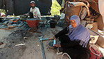 Aysha Ali, the wife of Ibraheem Mustafa, a 40-year-old Palestinian blacksmith, sharpens a handmade knife, as her husband hammers heated steel, at their small workshop in Gaza city on April 30, 2015. The ILO estimates that the 2014 conflict in Gaza raised unemployment from 32.6 per cent to 36.9 per cent, which caused an estimated daily loss in economic activity of US$ 508,000 per working day since August 2014. As the numbers of the unemployed laborers in Gaza reached 200,000 and poverty to 60 per cent, according to local reports. Photo by Ashraf Amra