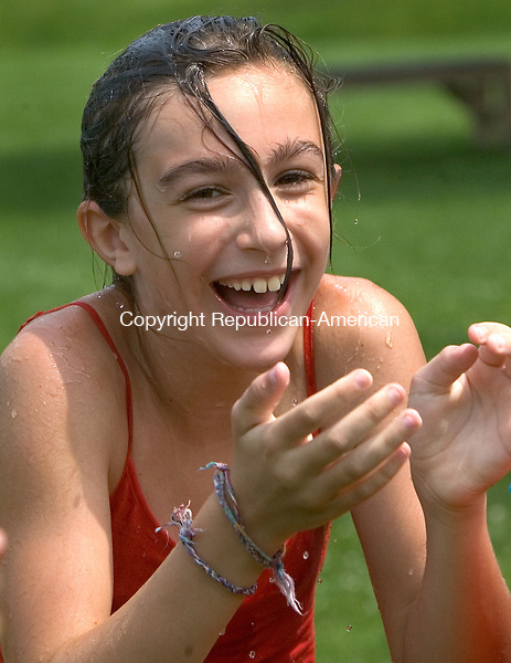 MIDDLEBURY CT. 06 July 2015-070615SV02-Maddie Kelly, 10 of Middlebury gets a little wet while playing a version of duck duck goose with water at playground camp sponsored by Park and Recreation in Meadowview Park in Middlebury Monday.<br /> Steven Valenti Republican-American